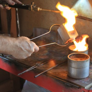 Ildanach Studios Copyrighted Image 2011 - Curtis Hands - pouring bronze into mold - Web - Ken Jensen Photography